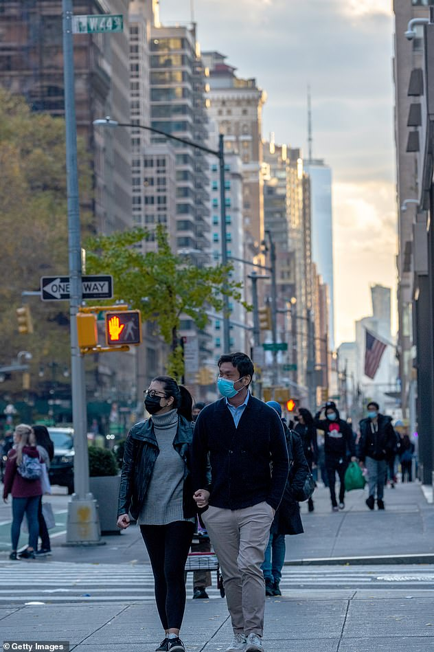 People wear masks as they walk along Fifth Avenue with One World Trade Center in New York City on November 28 (pictured) as America suffers a second wave of covid