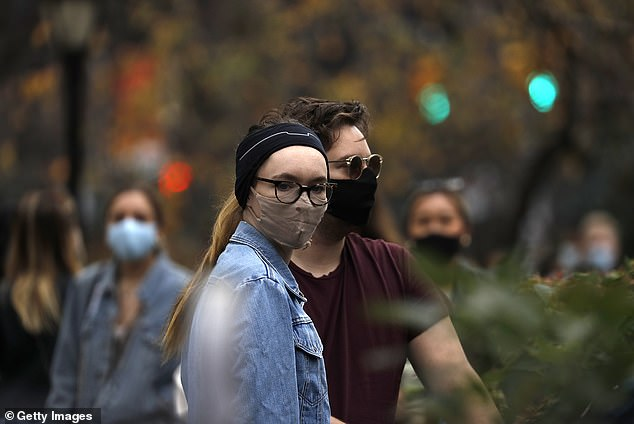 A couple wearing protective masks as they walk through Madison Square Park in New York City on November 21
