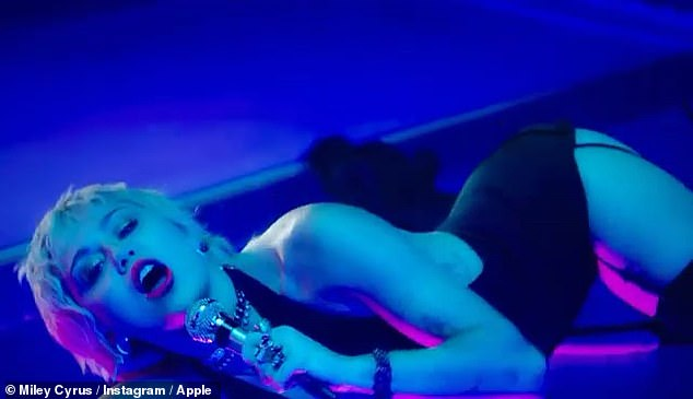 Edgy: Rocking a plunging black bodysuit, Cyrus writhed on a glass floor hovering above her pool as she sang the emotionally charged lyrics