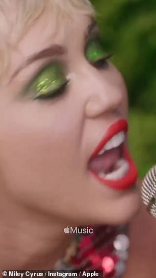 Medium in green: Sitting on a grass-covered sofa coordinated with her shimmering green eyeshadow, Miley showcased her enviably grated stamp