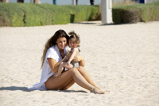 I shore do adore you: The mother-and-daughter bonding continued, as Amy was seen enjoying a cuddle with her adorable offspring as they sat on the beach together