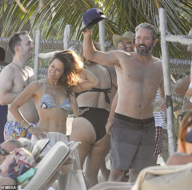 Toned: Brooke's enviable abs were on display in two pieces while Scott opted for a pair of ombre gray swim shorts