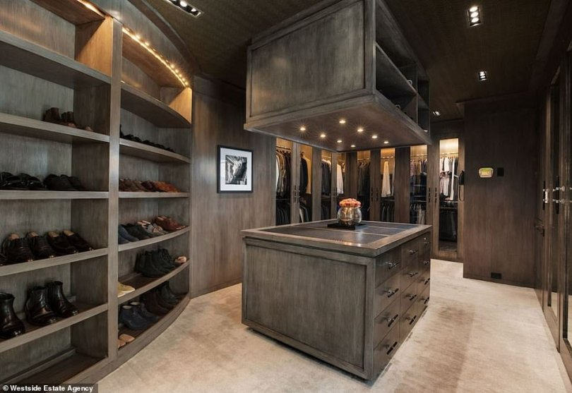 Clothes minded:The walk in closet is as big as most bedrooms in Los Angeles if not bigger. The style is decidedly male with brown/beige wood shelves and walls as well as a golden beige carpet