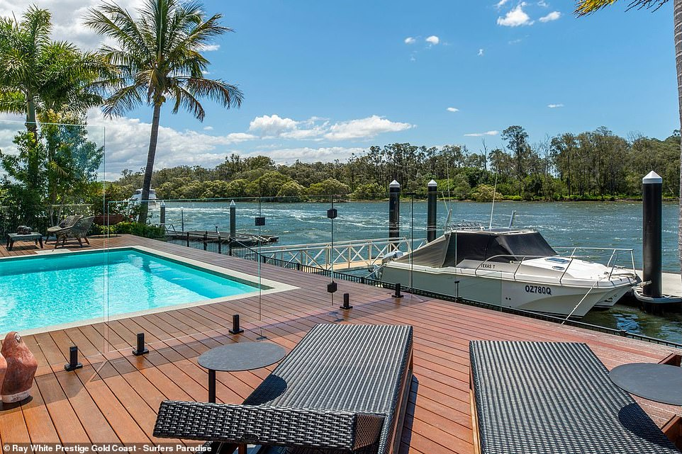 The outdoor entertainment deck has a swimming pool and built-in fireplace, both overlooking the Coomera River