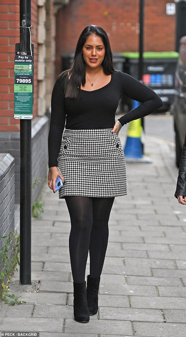 Malin Andersson puts on a chic display in a monochrome mini skirt and black jumper