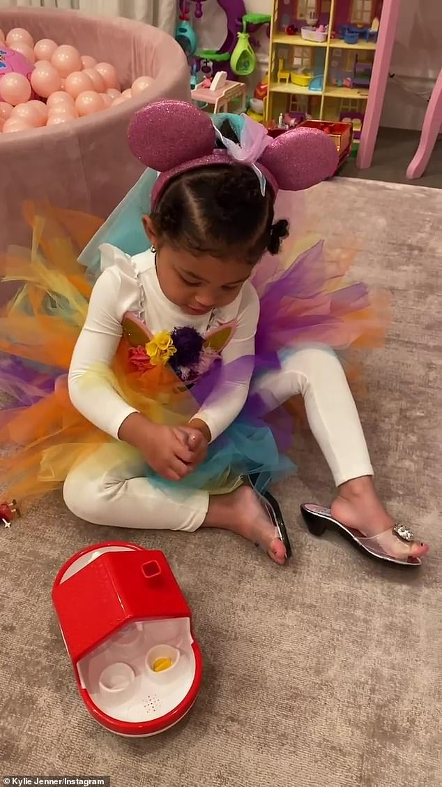 Child's play: Meanwhile, Kylie's daughter Stormi played with her toys wearing a bright tulle dress and heels