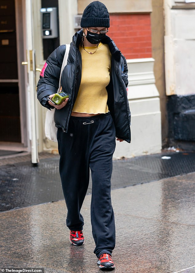 Mover and shaker:She teamed a puffy black anorak with a pair of matching sweats, adding a splash of color with a canary yellow crop top and red sneakers