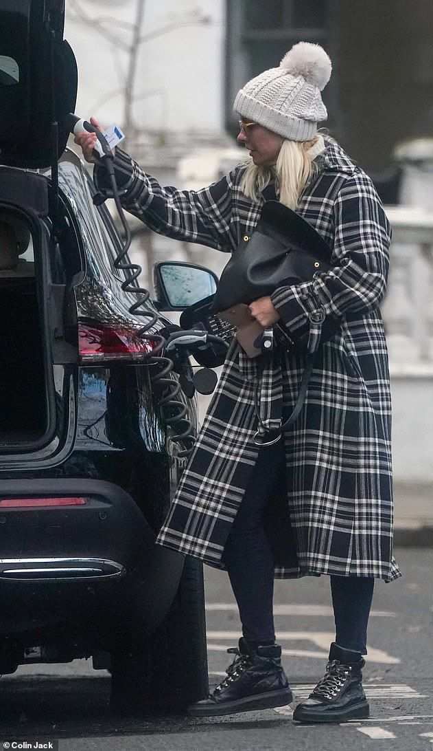 Going green: The This Morning presenter, 39, who also shares her eldest kid Harry, 11, with husband Dan Baldwin, 45, charged her electric car after her stroll across the English capital