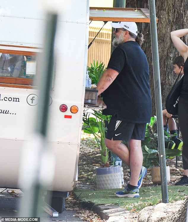 Relaxing: After showing off impressive swing, Russell fuelled up with a coffee from a nearby cart
