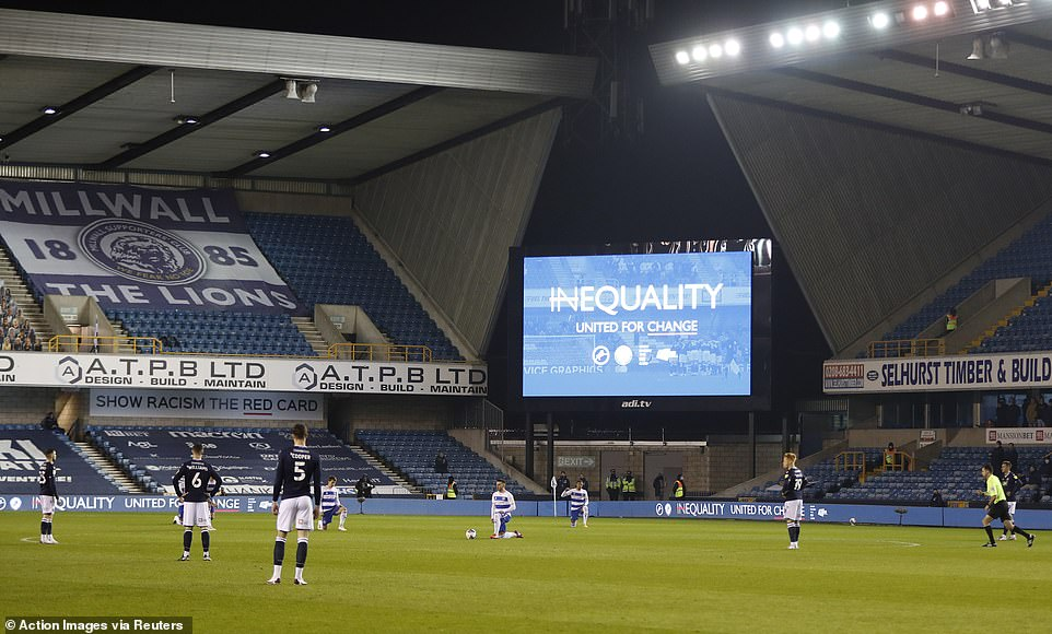QPR players kneel before the match while a large TV screen says 'Inequality, United for Change'