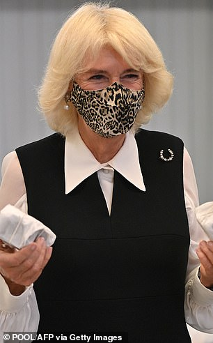 Fun with fabrics: Camilla in a leopard print mask on an engagement in London in October