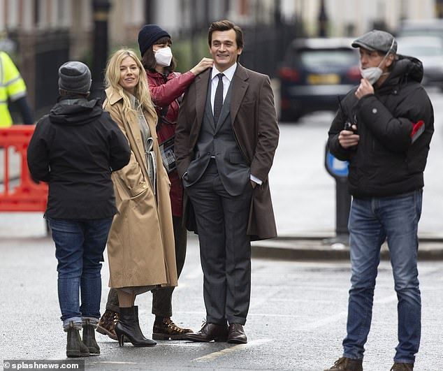 Happy: The duo chatted to crew members who prepared them for the scene, which saw the couple being chased by photographers