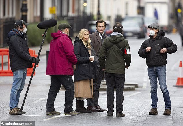 Quick break: Sienna covered her outfit in a long black padded coat to keep warm between scenes