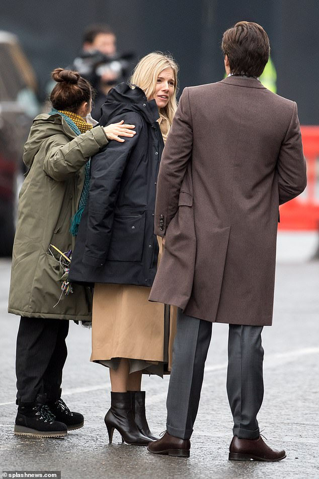 Nice and warm: The cast attempted to wrap up on their breaks between scenes due to the chilly December weather