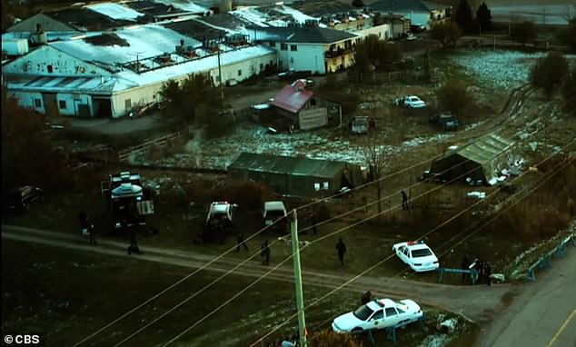 Scene of the crime: In the video, the camera pans over a forest of fall foliage, with quick shots of police cars surrounding a crime scene and a body being carried out of a river
