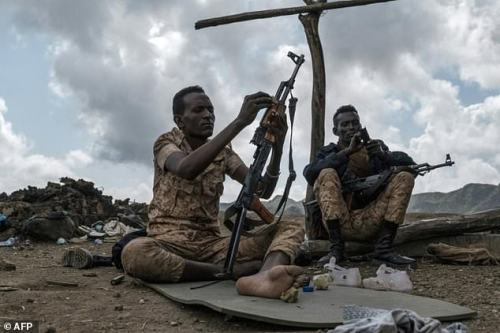 Members of the Afar special forces clean their weapons in the Tigray village of Bisober, the scene of clashes between regional and federal troops