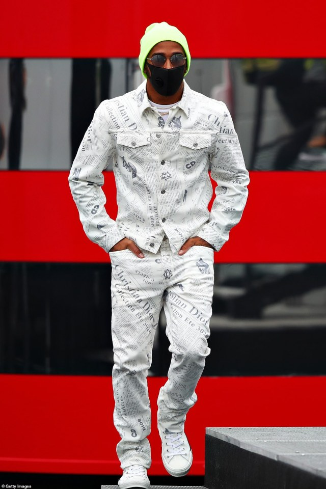 Hamiltondonned a newspaper-print co-ord, comprising of a denim shirt and straight-leg jeans, from French fashion house Dior as he strolled through the paddock ahead of thethe F1 Eifel Grand Prix at Nuerburgring. He finished the outfit with a fluorescent green beanie