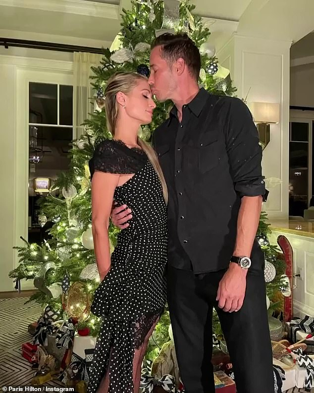 Gift of love: Paris Hilton, 39, shares a sweet photo with boyfriend of a year Carter Reum, 39, as she writes 'All I want for Christmas is you,' while he gives her a sweet forehead kiss by a lit up tree