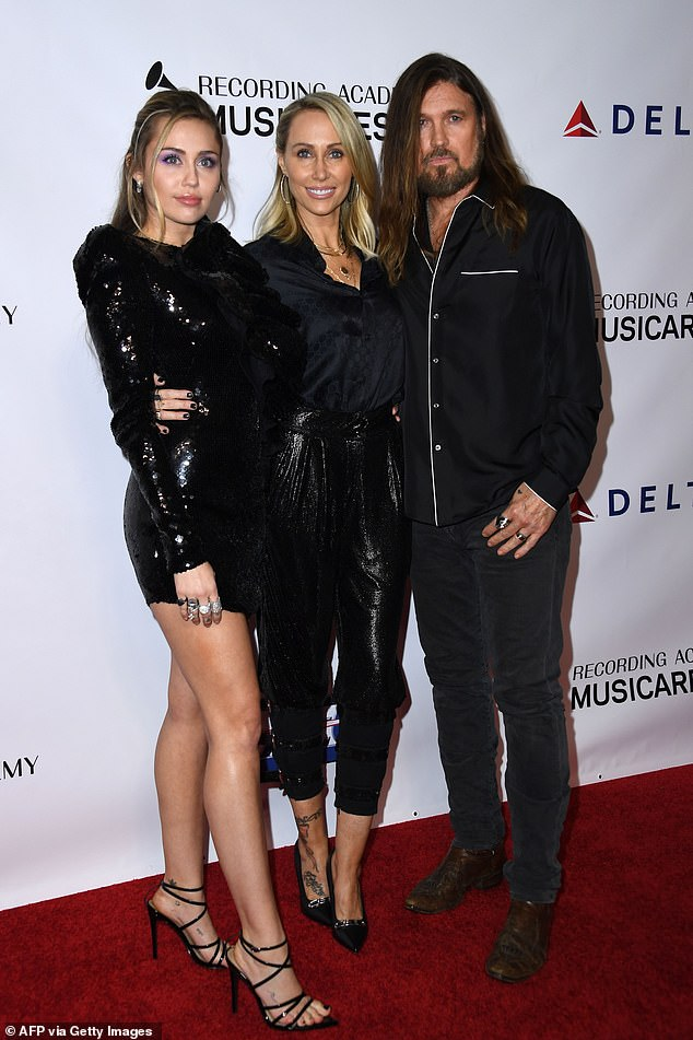 'It ends in a fist fight' Singer Miley Cyrus, 28, has reveals her very quirky Christmas traditions admitting they are 'unique' to her famous family. Pictured: parents Tish and Billy-Ray. LA, 2019