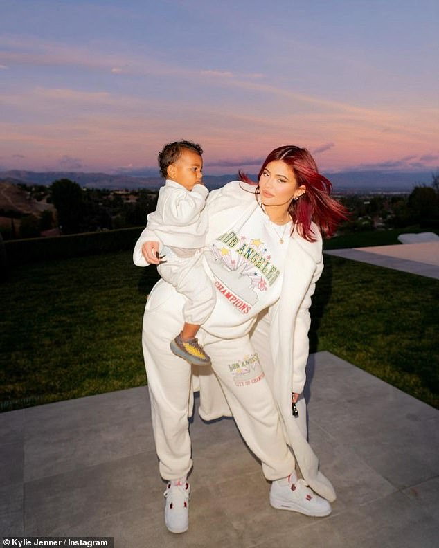Coolest: Deeming herself 'the cool aunt,' Jenner rocked an edgy ensemble as she cradled Psalm in her arms