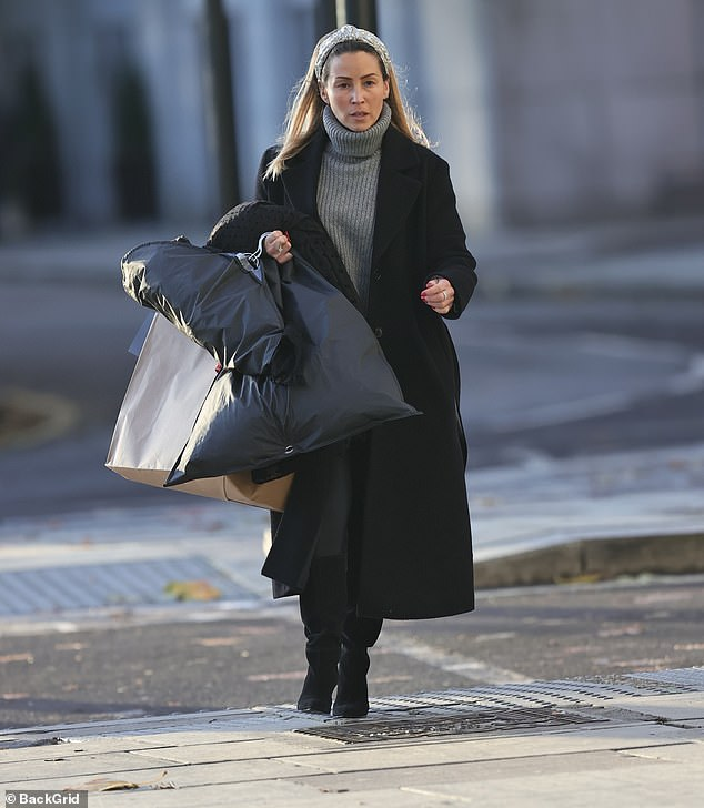 Laden down: The singer, 42, toted several bags and a large suit carrier as she made her way around the city