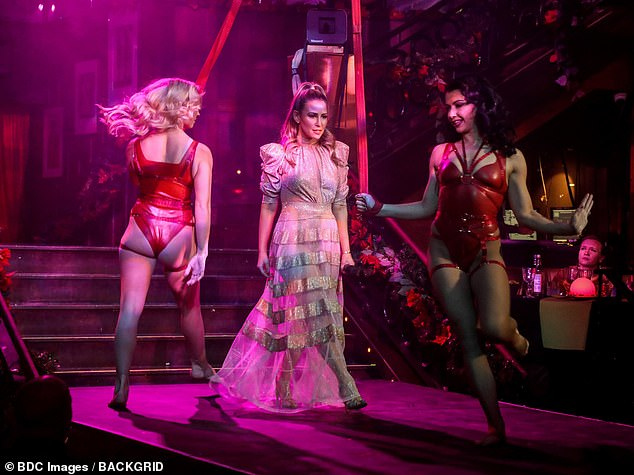 Wow! Rachel looked sensational in a glitzy pink dress with semi-sheer panels in the skirt as she hosted Cabaret All Stars last Wednesday (pictured with two performers during the show)