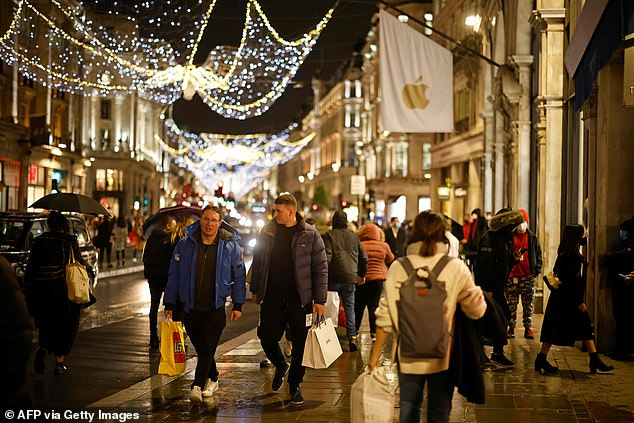 As part of the festivities, up to three households are allowed to meet for five days between December 23 and 27.  Shoppers on Regents Street pictured yesterday