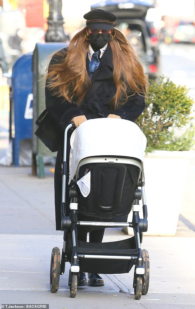 City slicker: The 25-year-old model looked effortlessly stylish, dressed in a long black trench coat while pounding the sidewalk through city streets with her little one