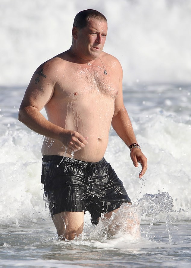 Karl Stefanovic strips off his shirt for a swim at the beach in Queensland
