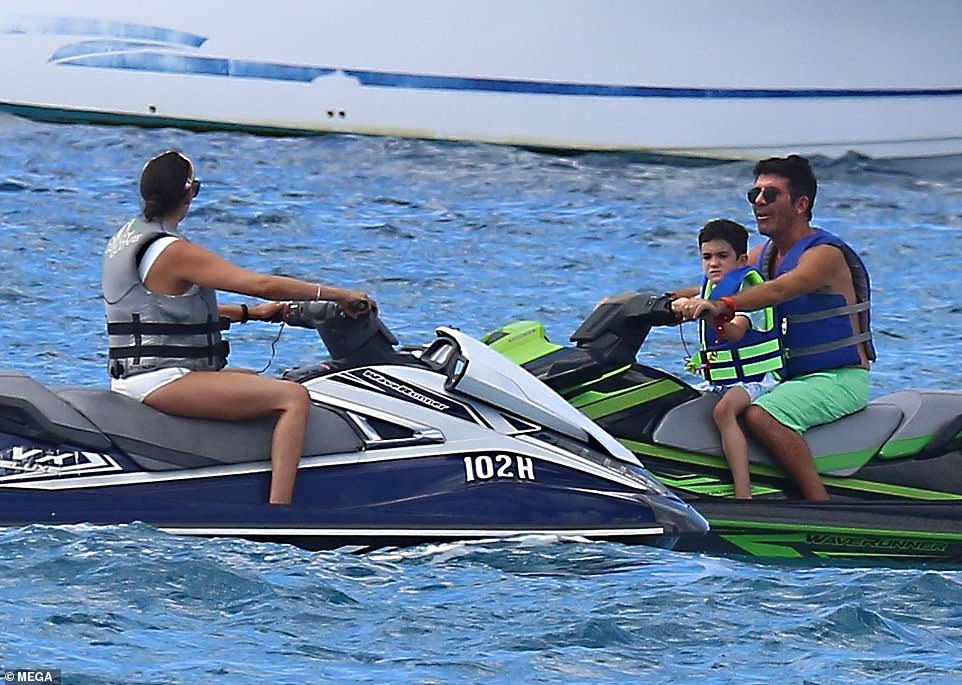 Family outing: Simon, Lauren and Eric looked every inch the happy family as they sped through the ocean on their jet skis