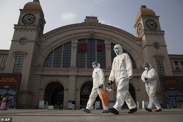 Pictured: Workers in protective suits walk past Hankou Station in Wuhan, China's Hubei Province, in April 2020. Wuhan is believed to have been the location of the Covid-19 outbreak, which triggered the pandemic world, has started.  The first case was reported on December 31, 2019