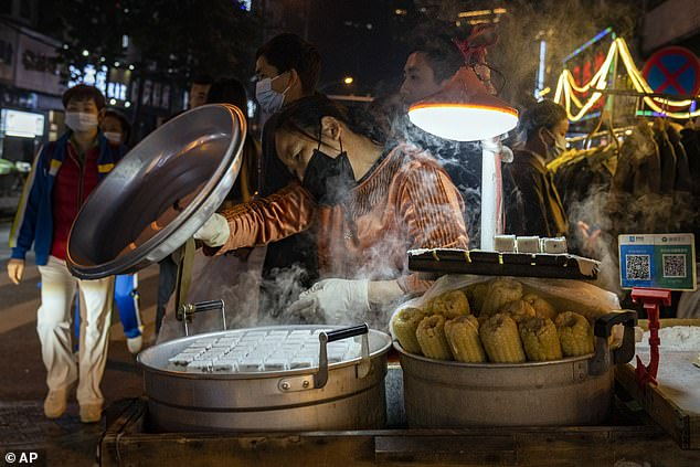 China reported the first cases of pneumonia of unknown cause in Wuhan, central China, to the WHO on December 31 and closed a so-called `` wet market '' where the new coronavirus is believed to have emerged.  Pictured: A street vendor prepares steamed specialties in Wuhan