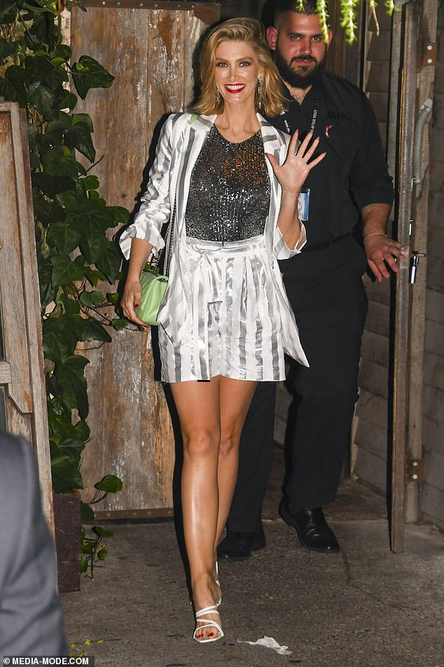 Absolute bombshell: Delta teamed her white and grey outfit with a sparkly singlet and an off-the-shoulder green leather purse, which was one of two statements on her outfit