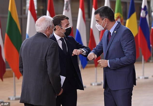 Spain's Prime Minister Pedro Sanchez, right, greets French President Emmanuel Macron, center, with an elbow bump during arrival for an EU summit at the European Council building in Brussels on December 10