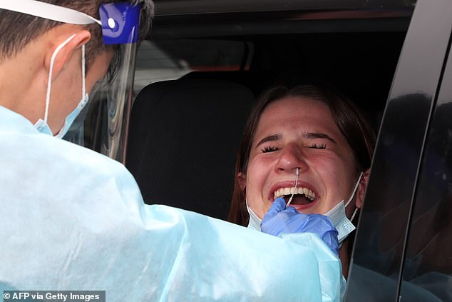 The coronavirus cluster on Sydney's northern beaches rose to 68. In the photo, a local resident gets tested at a drive-thru clinic on Sunday