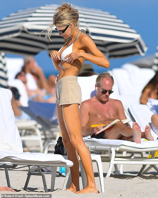 Revealing: She put on a sizzling display by showing off her cleavage in a ribbed white string bikini top, which she paired with beige shorts