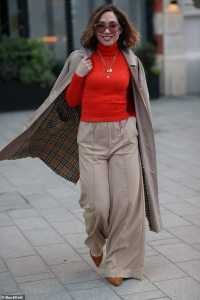 Myleene Klass cuts a chic figure in a scarlet sweater and cream flares