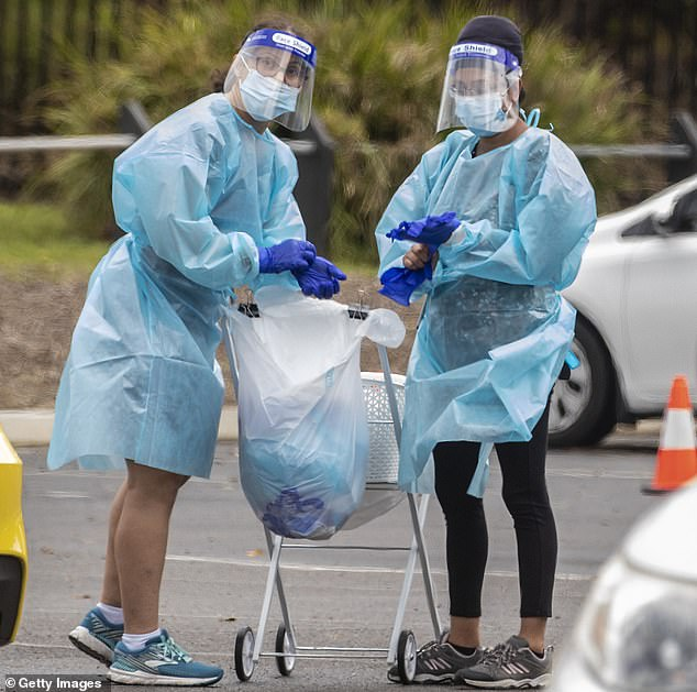 Nurses in full protective equipment on Sydney's northern beaches, amid a massive outbreak in the past week. That outbreak is linked to a US strain, rather than the UK variant