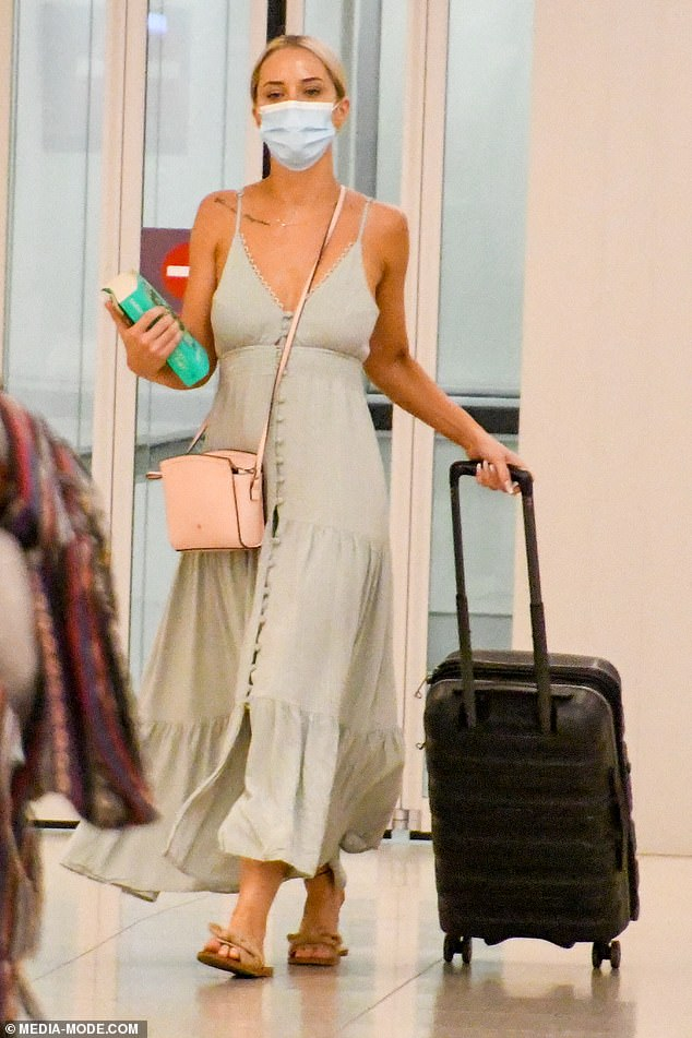 Christmas time: Jessika, who was flying into WA to spend the holidays with her family, wore a face mask and accessorised with a dainty necklace and cross-body bag