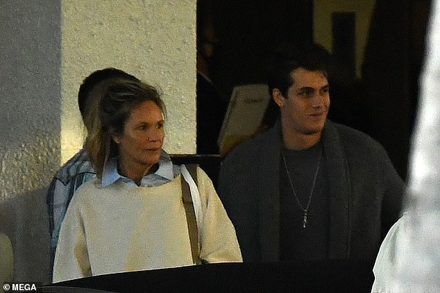 Here comes the son: She was accompanied by her 22-year-old son, Flynn, who was also seen without a face mask on