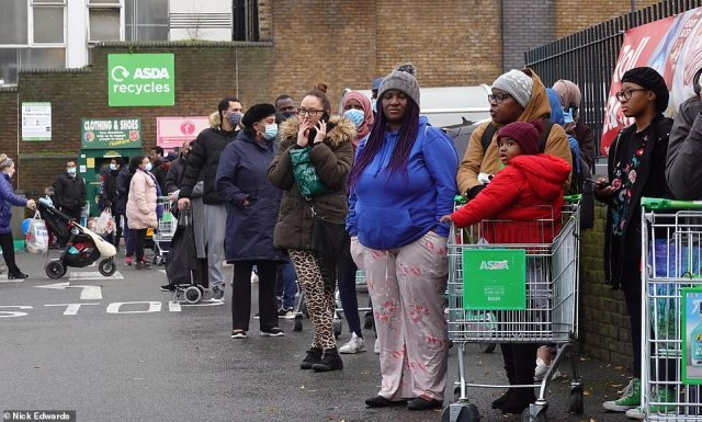 Shoppers outside Asda at Clapham Junction in South West London today as they pick up food for Christmas