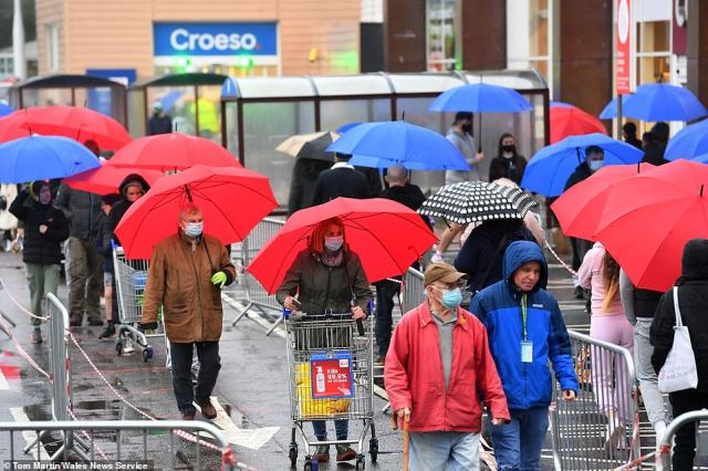 People took shelter from the rain as they queued outside a Tesco store in Cardiff, South Wales