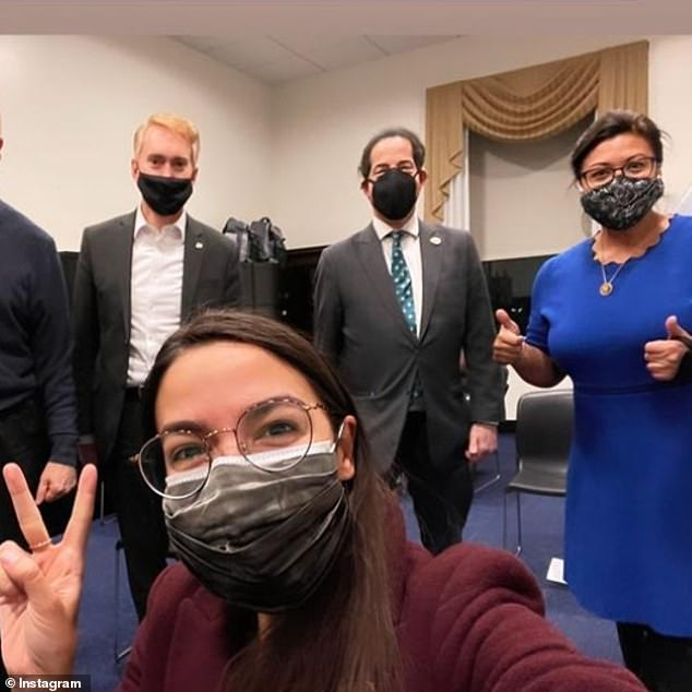 Rep. Alexandria Ocasio-Cortez (bottom) flashes a peace sign and is surrounded by Sen. James Lankford (left), Rep. Jamie Raskin (center), and Rep.Rashida Tlaib (right) as she took the jab Friday