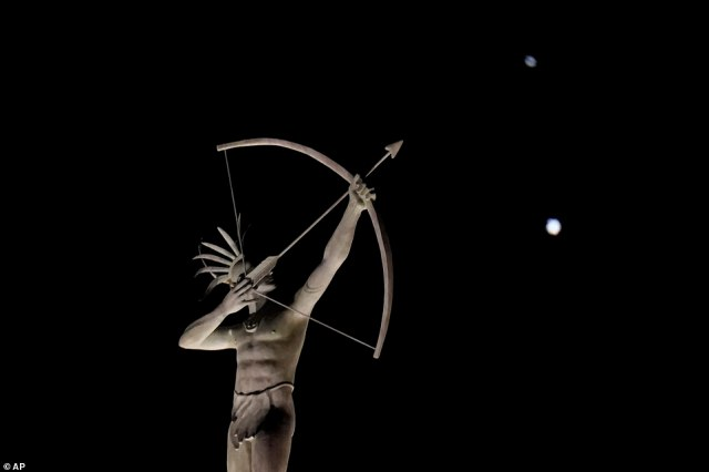 A statue of a Kansa Indian atop the Kansas Statehouse stands in the foreground as Saturn, top, and Jupiter, below, are seen Saturday, December 19, 2020 in Topeka, Kansas, US