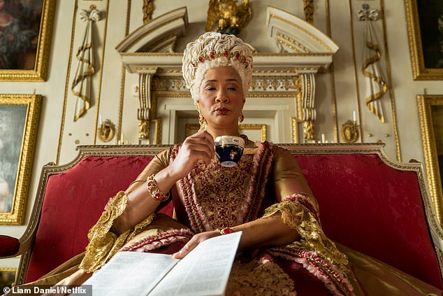 Pictured is Golda Rosheuval as Queen Charlotte sitting in the throne room in the new sex-filled show