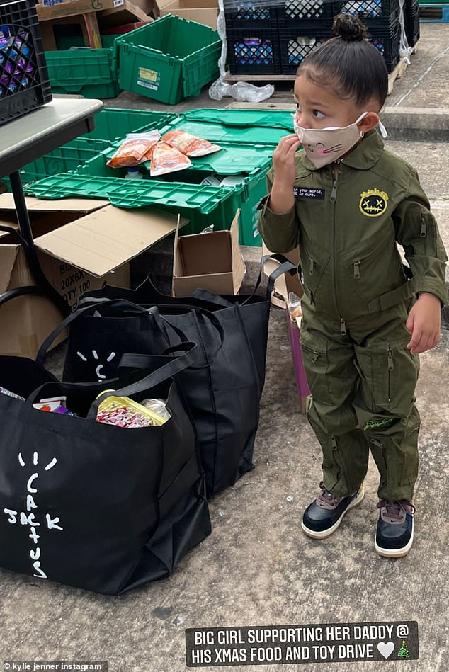 Family affair: Travis' ex Kylie Jenner was also present. She shared a photo of their daughter Stormi Webster, two, in a green jumpsuit. 'Big girl supporting her daddy @ his Xmas food and toy drive,' she wrote