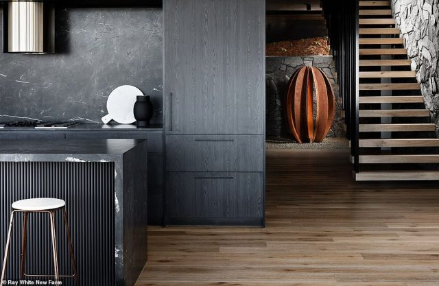 The very masculine black colour scheme flows through the home seamlessly - there are two kitchens in the home