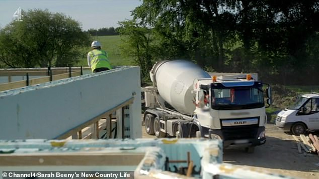 The truck that will pump the concrete into the walls through its 30 metre arm could be seen arriving on site (pictured)