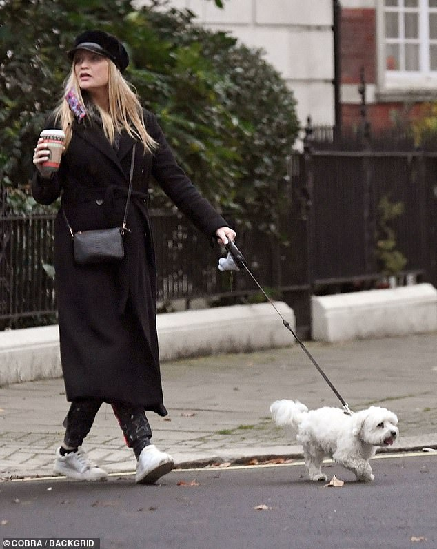 Trend: She wore comfortable black tracksuit bottoms, trainers and a bakerboy hat as she walked the dog, with her face mask hooked on one ear