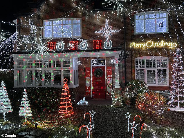 This house, in Wirral, the North West, has combined light-up signs with ornaments to create the perfect festive display